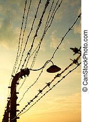 Auschwitz-Birkenau Concentration Camp - Barbed wire fence in...