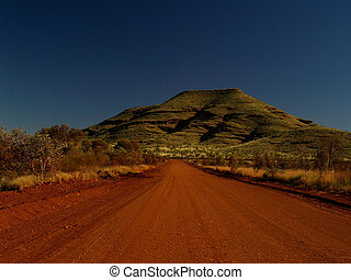 Australia Dirt Road with red Sand in front of green Hill
