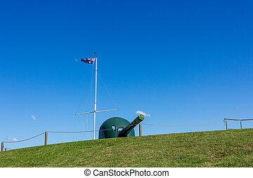 Australia flag waving on flagstaff and Vintage Cannon against blue sky at Newcastle, Australia .