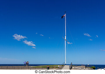 Australia flag waving on flagstaff over the sea and blue sky at Newcastle, Australia .