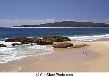 Australia, New South Wales , Booti Booti National Park, promenaders on South West Rocks Beach; sandy beach with wide view of the Pacific ocean and coastline in the background on a sunny day with  blue