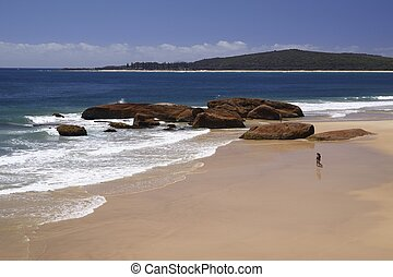 Australia, New South Wales , Booti Booti National Park, two promenaders walking towards the ocean on South West Rocks Beach; sandy beach with wide view of the Pacific ocean and coastline in the backgr