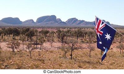SLOW MOTION: waving Australian flag in the blue sky with Kata Tjuta or The Olgas in Uluru-Kata Tjuta National Park on background. Red Centre in Northern Territory, Australia.