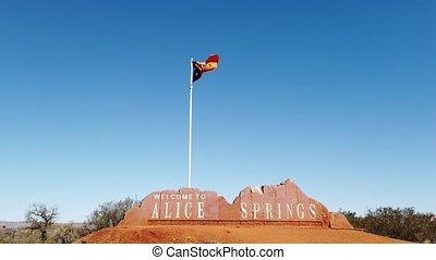 Australian Flag of Northern Territory of Alice Springs Welcome Sign and in Central Australia. Tourism in Outback Red Center desert. Blue sky with copy space.