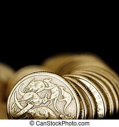 Australian one dollar coins over black background.