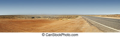 Panorama of the Australian Outback with red dirt and remote road