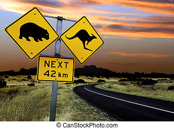 A road sign in the outback of Australia. Focus is on the sign - landscape is slightly out of focus.