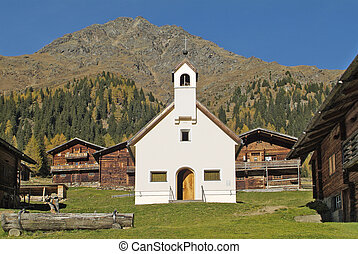 Austria, chapel and alpine huts to rent on Staller Alm in East Tyrol  in Villgraten valley, a beautiful area in Hohe Tauern national park in the Austrian Alps and a popular hiking area
