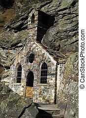 Austria, ctiny hapel built into rock named Felsenkapelle - Rock Chapel in Gschloess Valley, East Tyrol in National Park Hohe Tauern