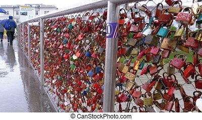 AUSTRIA, SALZBURG , MAY 12, 2019: Many Colorful Locks Hanging on Handrails on Love Bridge in Salzburg, Austria. Makartsteg Bridge covered in love locks with pedestrians walking over the Salzach River, City Centre. Rainy Weather