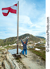 Austrian Flag above Alps mountain and Grossglockner High Alpine Road and jumping woman - tourist near