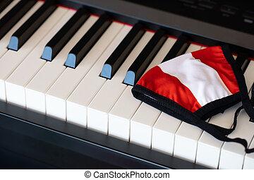 Austrian flag fabric mask on piano keyboard. Closeup