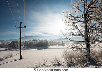 Austrian Winter Wonderland with mountains, a power pole in ...