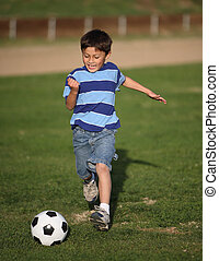 Latino boy playing with soccer ball