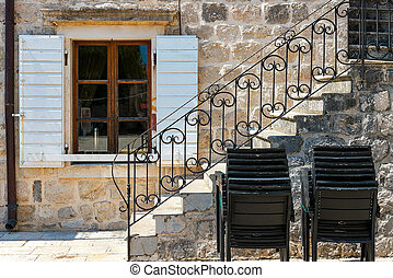 Authentic house with a stone wall and a beautiful window with shutters, with a side staircase, in the foreground piled chairs, background.
