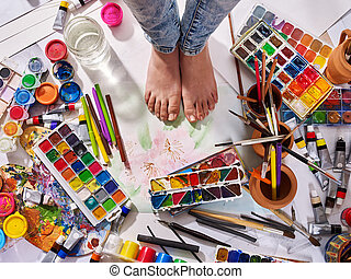Authentic paint brushes still life on floor in art class school.