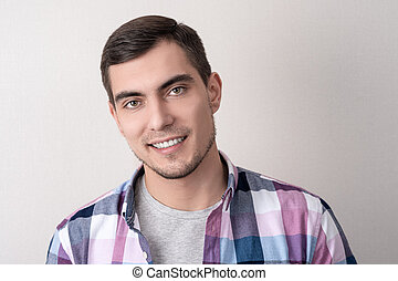 Authentic portrait of caucasian man in checkered pink shirt with perfect white smile on grey background