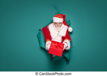 Authentic Santa Claus giving red christmas gift to the camera.