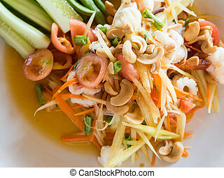 Authentic traditional salad with green papaya, fresh vegetables and herbs, seafood on plate in Thai restaurant