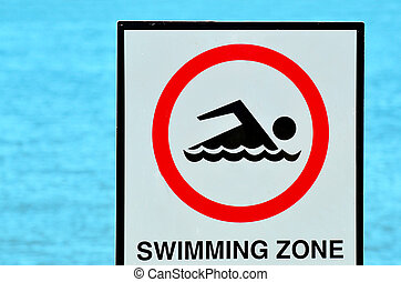 Authorise swimming zone sign against blue water background.