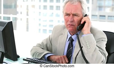 Authoritarian boss on the phone sitting in his office