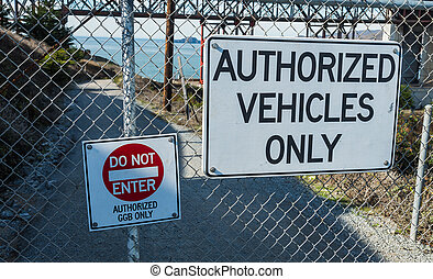 Authorized vehicles  only sign on steel fence