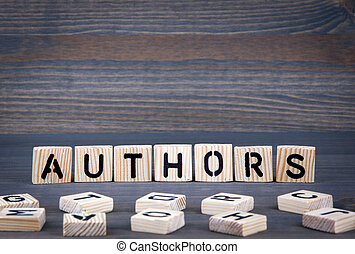Authors word written on wood block. Dark wood background with texture
