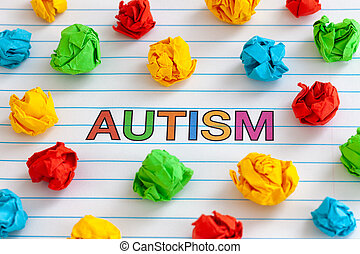 Autism spectrum disorder. Autism word on notebook sheet with some colorful crumpled paper balls around it