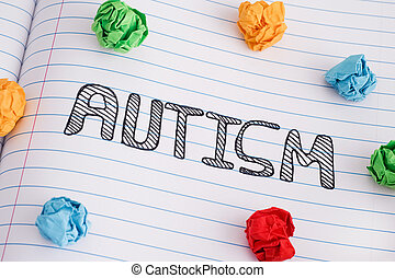 Autism word on notebook sheet with some colorful crumpled paper balls on it