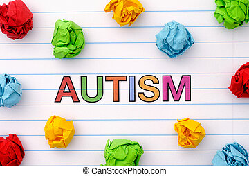 Autism word on notebook sheet with some colorful crumpled paper balls around it