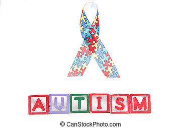 Autism awareness ribbon above letter blocks spelling autism...