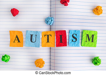 Word Autism on notebook sheet with some colorful crumpled paper balls around it