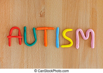 Autism word made out of play dough. Wooden background