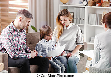 Autistic boy describing picture while sitting with parents during consultation with therapist