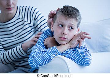 Autistic child lying on sofa