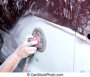 Auto body shop sanding - Worker is sanding filler with air...