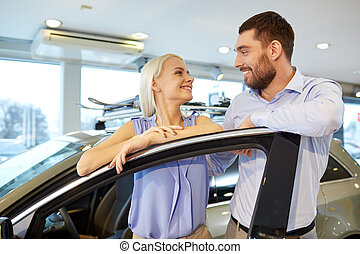 happy couple buying car in auto show or salon