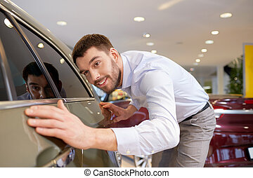 happy man touching car in auto show or salon - auto business...