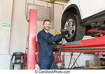 Auto Engineer Fixing Tire Nuts With Electric Spanner In Garage