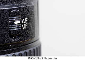 Black and white image of an automatic and manual focus switch on a camera lens