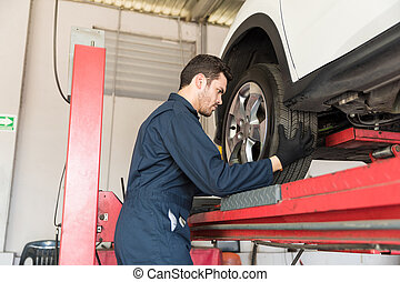 Auto Mechanic Adjusting Car Tire In Repair Shop