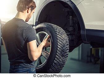Mechanic adjusting tire wheel at repair garage
