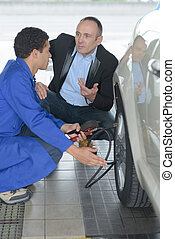 auto mechanic and client in tire service