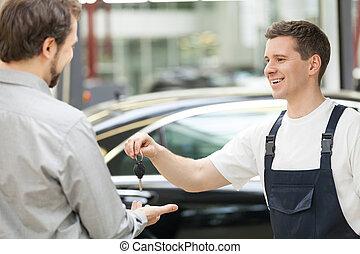 Auto mechanic and customer. Cheerful auto mechanic giving a...