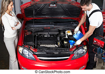 Auto mechanic and woman in auto repair shop.