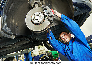 auto mechanic at car brake shoes examining