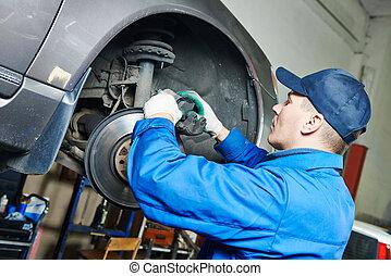 auto mechanic at car brakes repairing