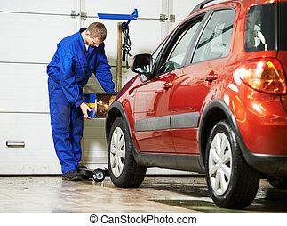 auto mechanic at car headlight checkup