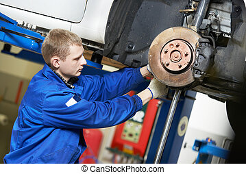 auto mechanic at car suspension repair work - car mechanic...