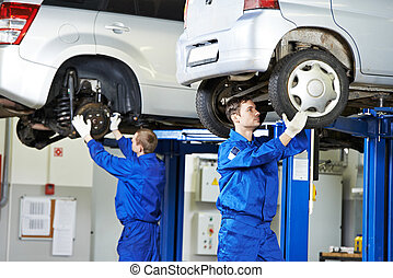 car mechanic inspecting car wheel and suspension detail of lifted automobile at repair service station